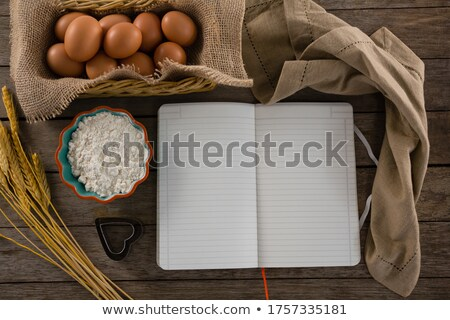 Book, eggs, flour, cookie cutter and cloth kept on a table Stock photo © wavebreak_media