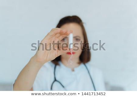Woman doctor in latex gloves with tampon Stock photo © Traimak