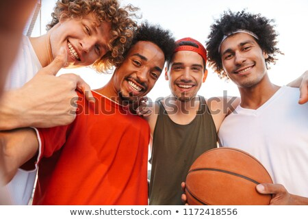 photo of multiethnic men playing basketball at the playground ou stock photo © deandrobot