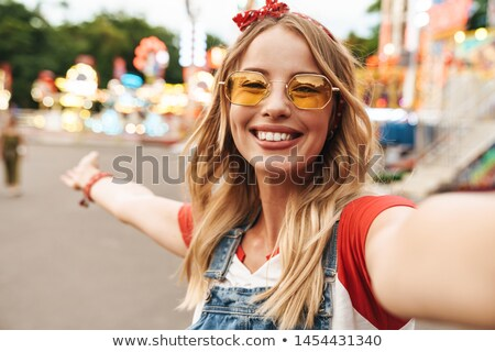 Image of amusing blond woman smiling and taking selfie photo, is Stock photo © deandrobot