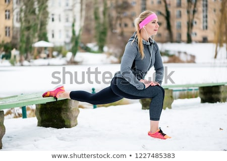 Woman stretching her limbs for sports exercise in winter Stock photo © Kzenon