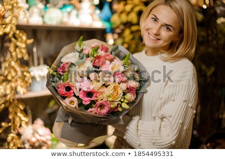 Smiling girl florist with beautiful bouquet in her hands on a light background with green leaves. Mo Stock photo © artjazz