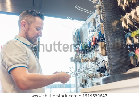 Man at key cutter shop looking at blanks Stock photo © Kzenon