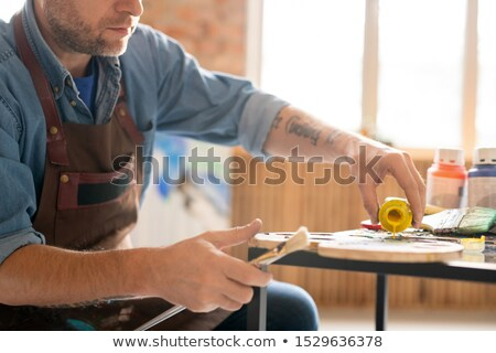 Contemporary artist pouring liquid yellow gouache on palette Stock photo © pressmaster