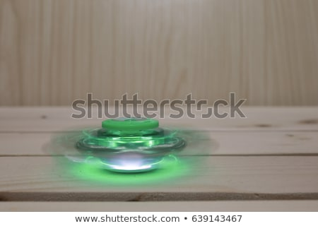 A man hand holding hand spinner or fidget spinner over wooden background Stock photo © galitskaya