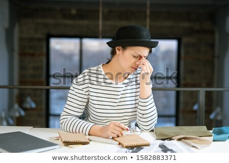 Tired young female designer in hat and striped pullover trying to concentrate Stock photo © pressmaster