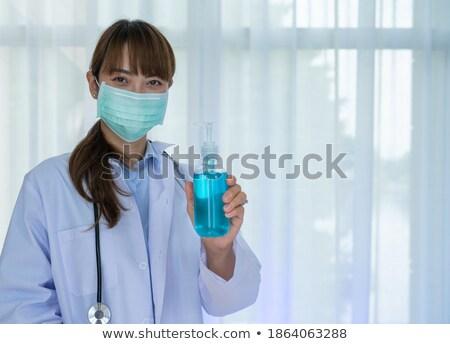 Portrait of a doctor using an antibacterial gel Stock photo © majdansky