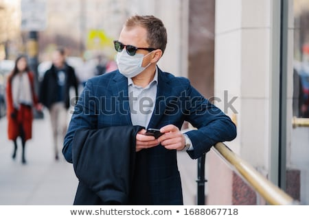 Prosperous businessman in formal wear poses at street, waits for someone, holds mobile phone and sen Stock photo © vkstudio
