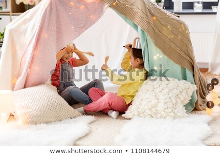 girls with pots playing in kids tent at home Stock photo © dolgachov