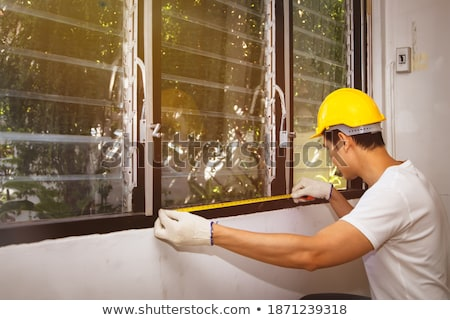 Carpenter Measures the Old Window Stock photo © Voysla