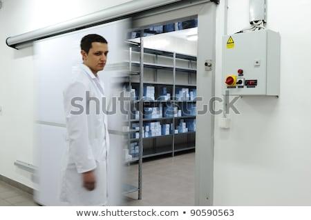 Young worker opening  door of industrial refrigerator  Stock photo © zurijeta