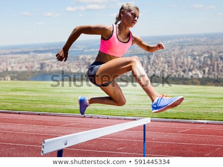 Composite image of sporty woman jumping a hurdle Stock photo © wavebreak_media