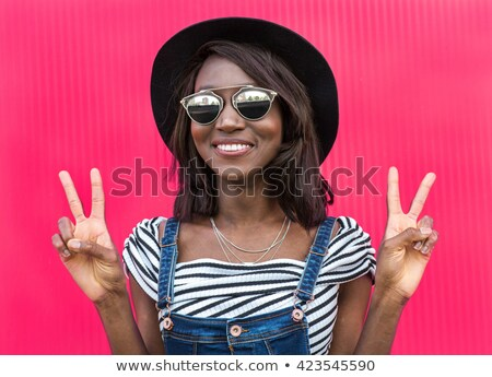 pretty woman wearing glasses posing over pink background stock photo © deandrobot