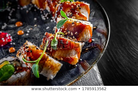 Grilled smoked eel on black plate Stock photo © lunamarina