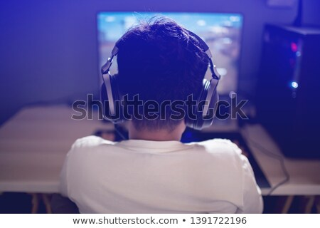 Portrait of asian gamer boy playing video games on computer in d Stock photo © deandrobot