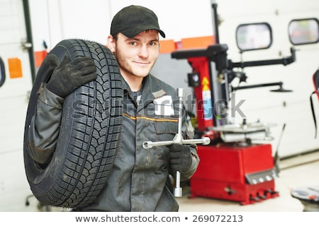 Portrait of a mechanic replacing a wheel Stock photo © Minervastock