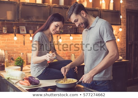 loving couple preparing pasta in the kitchen stock photo © boggy