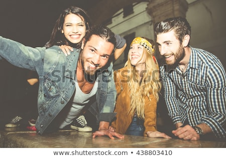 group of young hippy men and women smiling and taking selfie on stock photo © deandrobot