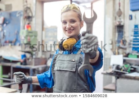 Stock photo: Woman mechanic showing tools to the camera