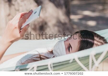 женщину гамак торговых онлайн мобильного телефона пляж Сток-фото © AndreyPopov