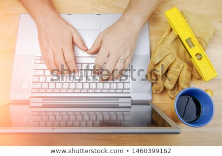 Work Gloves, Level and Coffee Cup Next To Contractor Reviewing P Stock photo © feverpitch