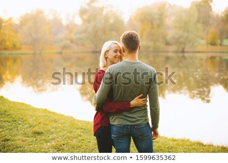 happy young man near the lake outdoor on a autumn day stock photo © dashapetrenko