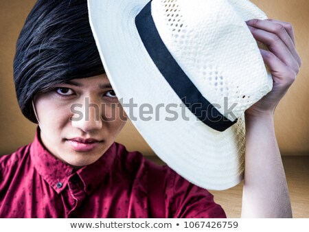 Close up of millennial man tipping hat against brown room Stock photo © wavebreak_media