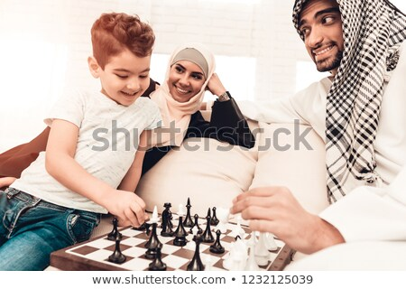 boy playing chess at home with mother stock photo © lopolo