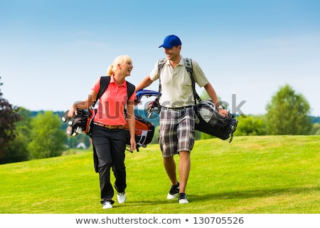 Woman golf player walking on golf course. Stock photo © lichtmeister