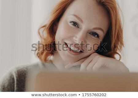Indoor shot of satisfied good looking redhead female sits on floor, keeps legs crossed, ballet barre Stock photo © vkstudio