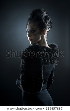A gothic woman over a dark background, Stock photo © Lopolo
