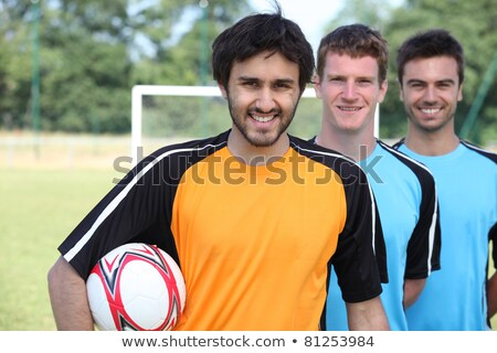 Stock photo: Three footballers in a line-up in front of goal