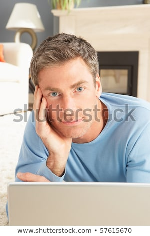 Man Using Laptop Relaxing Laying On Rug At Home Stock photo © monkey_business