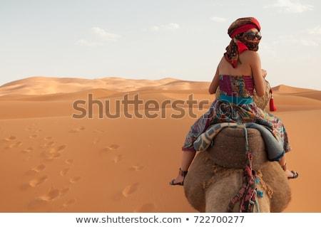 Woman leading camel across desert Stock photo © monkey_business