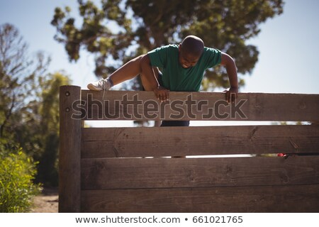 boy climbing wooden wall during obstacle course stock photo © wavebreak_media