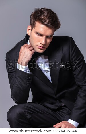 seated man holding his suit collar looks down to side Stock photo © feedough
