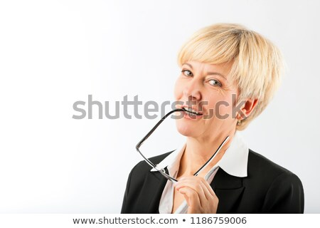 Mature businesswoman with eyeglasses earpiece in mouth Stock photo © Kzenon