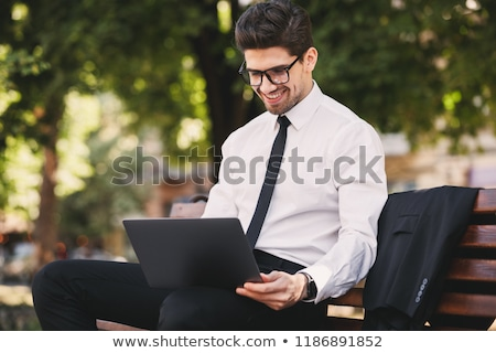 Photo of handsome man in businesslike suit sitting on bench in g Stock photo © deandrobot