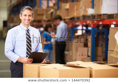 happy businessman with clipboard at warehouse stock photo © dolgachov
