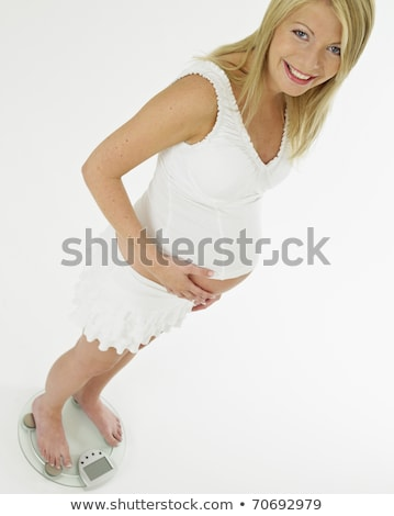 pregnat woman standing on weight scale stock photo © phbcz