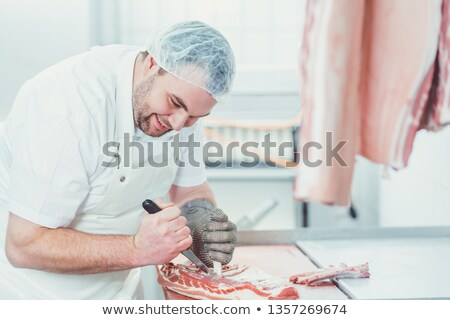 Meat being processed in a butchery by man Stock photo © Kzenon