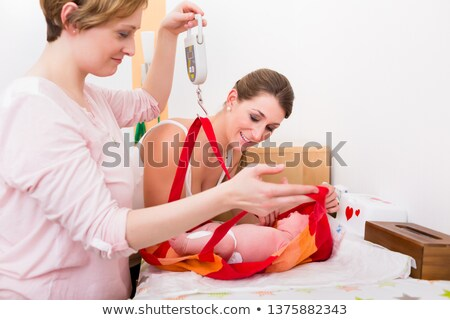 Women looking at baby in the weighing bag Stock photo © Kzenon