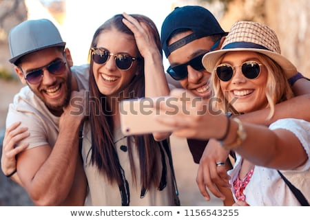 Group of cheerful young friends having fun time together Stock photo © deandrobot