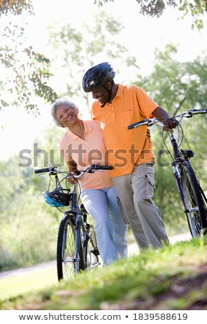 Low angle view of happy senior couple walking with bicycle and looking each other on beach in the su Stock photo © wavebreak_media
