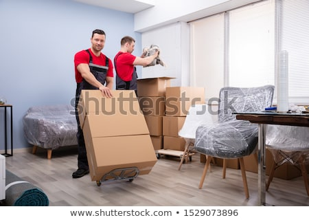 Portrait Of Two Young Movers With Stack Of Cardboard Boxes Stock photo © AndreyPopov