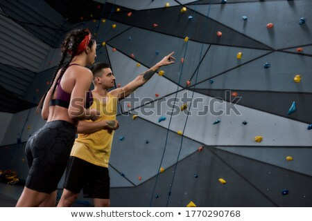 Young female or climbing instructor in activewear and safety belts Stock photo © pressmaster