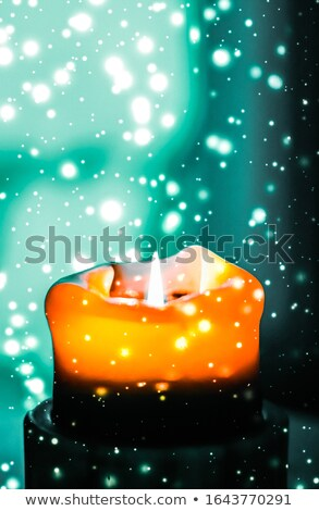 Orange holiday candle on green sparkling snowing background, lux stock photo © Anneleven