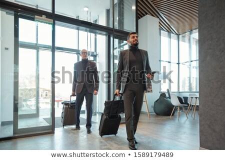 Kettő elegáns üzlet húz bőröndök hotel Stock fotó © pressmaster
