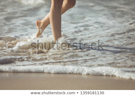 Low section of young Caucasian woman walking along the ocean at the beach on sunny day Stock photo © wavebreak_media