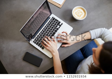 image of young caucasian woman using laptop and smartphone in ca stock photo © deandrobot